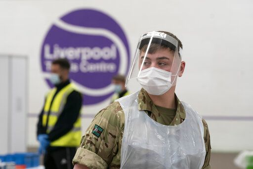 A member of the armed forces waits to test the public at Liverpool Tennis Centre on the first day of the pilot scheme of mass testing in Liverpool, Friday Nov. 6, 2020. Liverpool is the pilot project for possible weekly testing of the entire population, covering up to 10 million people across England a day.