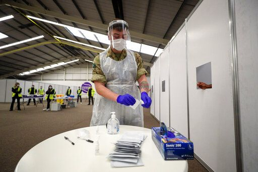 NHS staff and soldiers prepare the mass COVID-19 testing at the Liverpool Tennis Centre, Liverpool, England, Friday Nov. 6, 2020. Britain's lockdown started Thursday, shuttering restaurants, hairdressers and clothing stores until at least Dec. 2. (Peter Byrne/PA via AP)