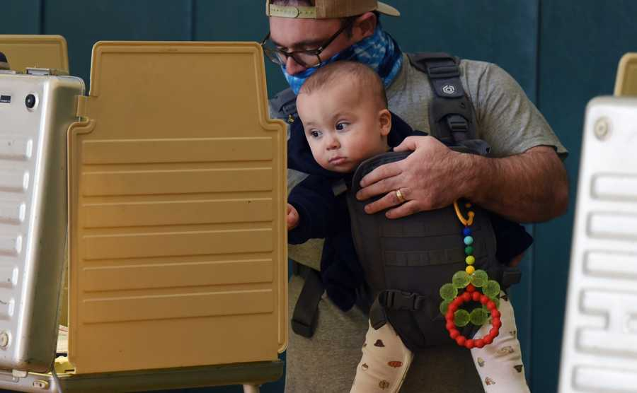 Brian Dunton holds his son, Jack, age 10 months, while voting at Greenbriar Elementary School in Northbrook on Election Day Tuesday.