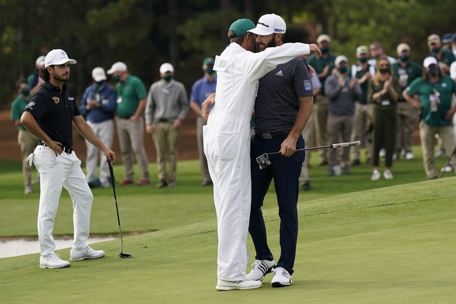 Dustin Johnson is hugged by his caddie Austin Johnson after winning the Masters golf tournament Sunday, Nov. 15, 2020, in Augusta, Ga.