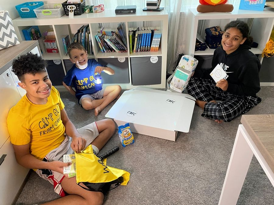 Isaac Parris, now 15, and his siblings, Eli Schippers, 6, and Ivy Parris, 14, pack all of the care packages for Camp Out From Cancer.
