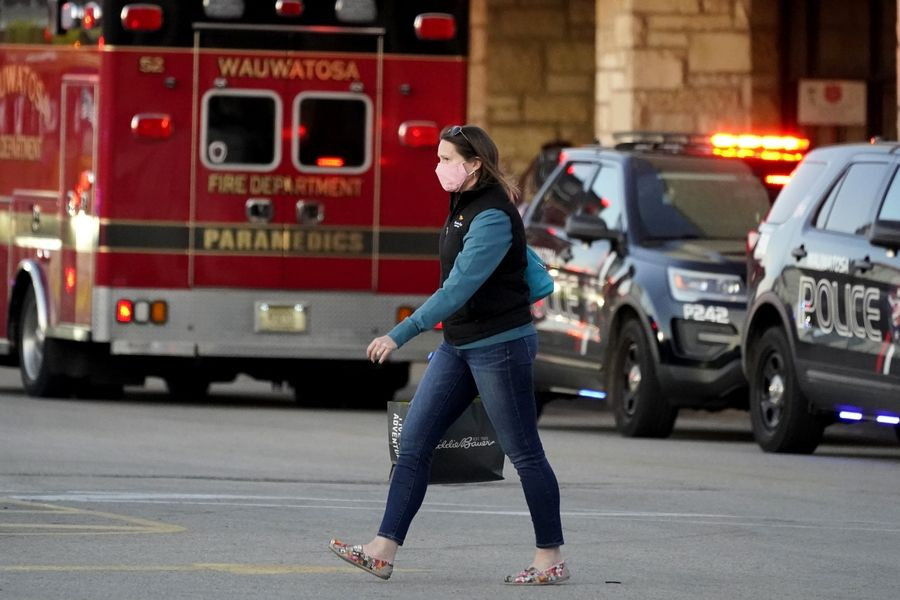 A shopper leaves the Mayfair Mall after a shooting, Friday, Nov. 20, 2020, in Wauwatosa, Wis. Multiple people were shot Friday afternoon at the mall, and police are still searching for the shooter.