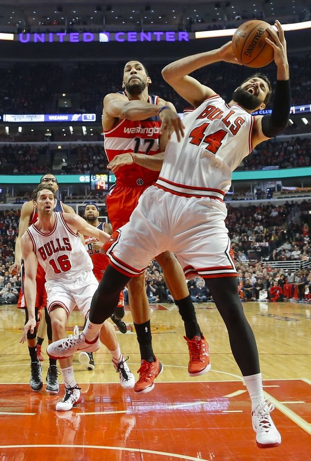 Chicago Bulls forward Nikola Mirotic (44) is fouled on the way to the basket by Washington Wizards guard Garrett Temple (17) during the first half of an NBA basketball game, Tuesday, March 3, 2015, in Chicago.