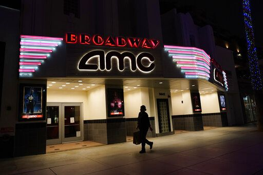 A shopper walks past a closed AMC movie theater Thursday, Nov. 19, 2020, in Santa Monica, Calif. California Gov. Gavin Newsom is imposing an overnight curfew as the most populous state tries to head off a surge in coronavirus cases. On Thursday, Newsom announced a limited stay-at-home order in 41 counties that account for nearly the entire state population of just under 40 million people.