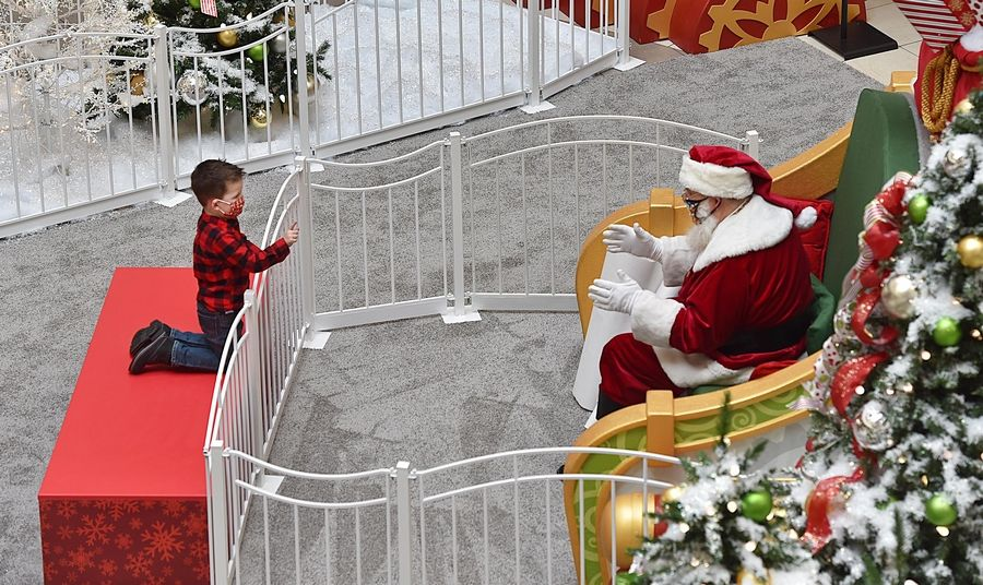 Patrick Walsh, 3½, gives Santa his wish list in person Friday at Fashion Outlets of Chicago Mall in Rosemont. Suburban malls are having socially distanced visits through Christmas Eve.