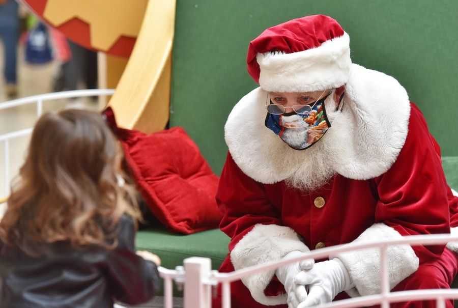 Santa wears a mask Friday as he visits with Viviana Drehobl, 2, at Fashion Outlets Mall in Rosemont.