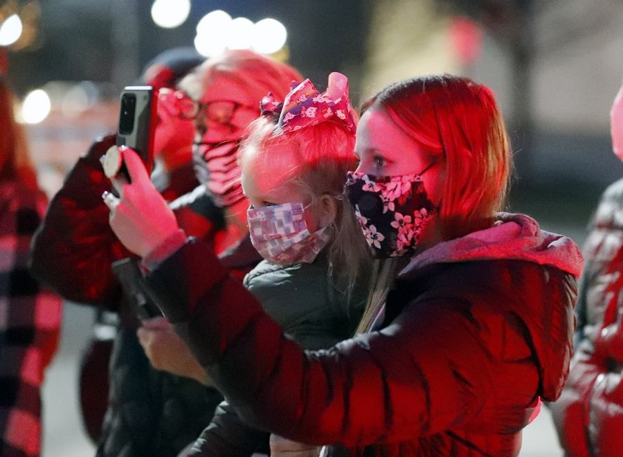 Lindsay Wyllie of Palatine takes a photo of Santa as she holds her daughter Jaylynn, 3, at the holiday tree lighting event near the intersection of Slade and Greeley streets Saturday in Palatine.