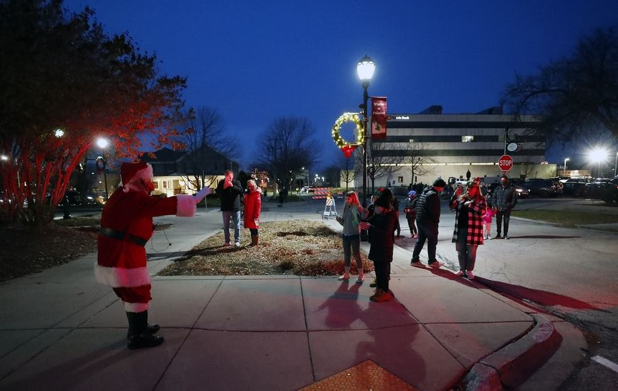 Santa gives a socially distanced wave to onlookers at the holiday tree lighting event near the intersection of Slade and Greeley streets Saturday in Palatine.