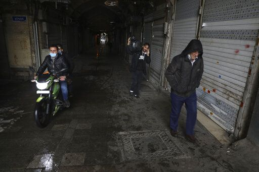 People leave the closed Tehran's Grand Bazaar, Iran's main business and trade hub, Satuday, Nov. 21, 2020. Iran on Saturday shuttered businesses and curtailed travel between its major cities, including the capital of Tehran, as it grapples with the worst outbreak of the coronavirus in the Mideast region.