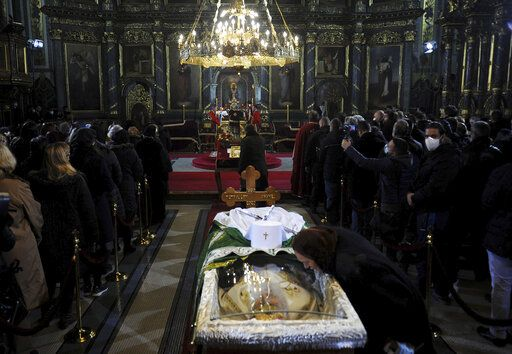 A woman kisses a protective screen over the coffin of Patriarch Irinej as he lies in repose at the Congregational church in Belgrade, Serbia, Saturday, Nov. 21, 2020. Mourners flocked to pay respects following the death of the Serbian Orthodox Church Patriarch Irinej, many ignoring preventive measures against the new coronavirus even though the head of the church died after contracting the virus himself.
