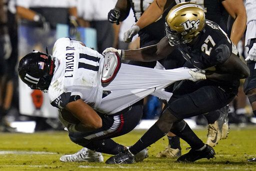 Cincinnati tight end Leonard Taylor (11) is stopped by Central Florida defensive back Richie Grant (27) during the second half of an NCAA college football game, Saturday, Nov. 21, 2020, in Orlando, Fla.