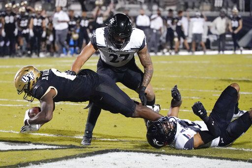 Central Florida wide receiver Marlon Williams, left, scores a touchdown as he gets past Cincinnati linebacker Darrian Beavers, center, and safety Darrick Forrest, right, during the second half of an NCAA college football game, Saturday, Nov. 21, 2020, in Orlando, Fla.