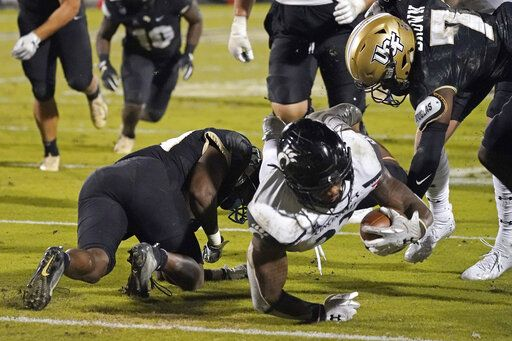 Cincinnati running back Gerrid Doaks, center, is stopped just short of the goal line by Central Florida defensive backs Derek Gainous, left, and Davonte Brown (7) during the second half of an NCAA college football game, Saturday, Nov. 21, 2020, in Orlando, Fla.
