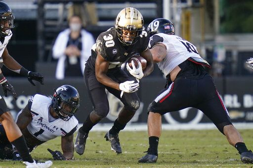 Central Florida running back Greg McCrae (30) runs for yardages against Cincinnati safety James Wiggins, left, and defensive tackle Ethan Tucky, right, during the first half of an NCAA college football game, Saturday, Nov. 21, 2020, in Orlando, Fla.
