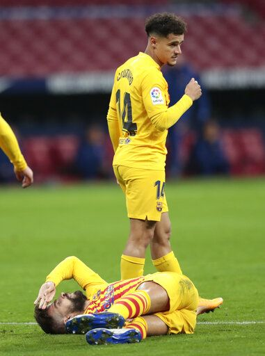 Barcelona's Gerard Pique, bottom, reacts after getting an injury during the Spanish La Liga soccer match between Atletico Madrid and FC Barcelona at the Wanda Metropolitano stadium in Madrid, Spain, Saturday, Nov. 21, 2020.