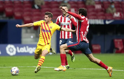 Barcelona's Sergi Roberto, left, is challenged by Atletico Madrid's Jose Gimenez during the Spanish La Liga soccer match between Atletico Madrid and FC Barcelona at the Wanda Metropolitano stadium in Madrid, Spain, Saturday, Nov. 21, 2020.