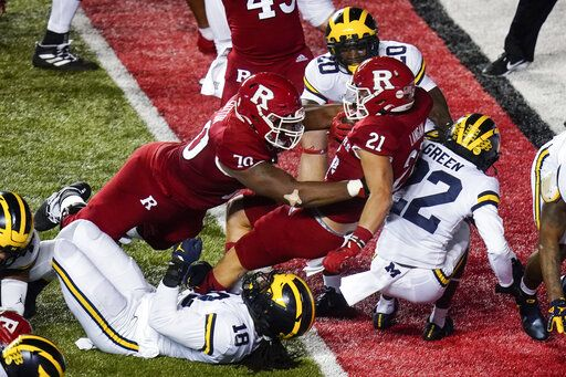 Rutgers' Johnny Langan (21) rushes against Michigan's Luiji Vilain (18) and Gemon Green (22) for a touchdown during the first half of an NCAA college football game Saturday, Nov. 21, 2020, in Piscataway, N.J.