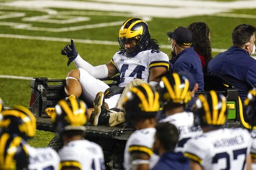 Michigan's Cameron McGrone (44) gestures to teammates as he is carted off the field after being injured during the first half of the team's NCAA college football game against Rutgers on Saturday, Nov. 21, 2020, in Piscataway, N.J.
