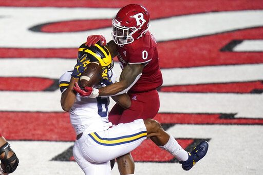Rutgers' Christian Izien defends against Michigan's Cornelius Johnson during the third overtime of an NCAA college football game Saturday, Nov. 21, 2020, in Piscataway, N.J. Michigan won 48-42.