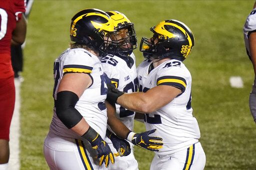 Michigan's Hassan Haskins (25) celebrates with Karsen Barnhart, left, and Ben Mason during the third overtime of an NCAA college football game against Rutgers on Saturday, Nov. 21, 2020, in Piscataway, N.J. Michigan won 48-42.