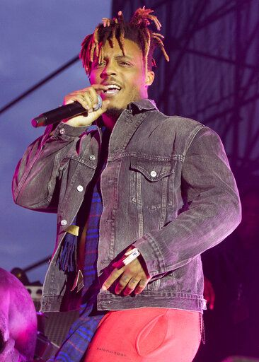 "FILE - In this May 15, 2019 file photo, Juice WRLD performs in concert during his ""Death Race for Love Tour"" at The Skyline Stage at The Mann Center for the Performing Arts in Philadelphia. The 21-track album ""Legends Never Die"" set several records when it debuted at No. 1 on the Billboard 200 albums chart, but failed to receive a Grammy nomination. (Photo by Owen Sweeney/Invision/AP, File)"