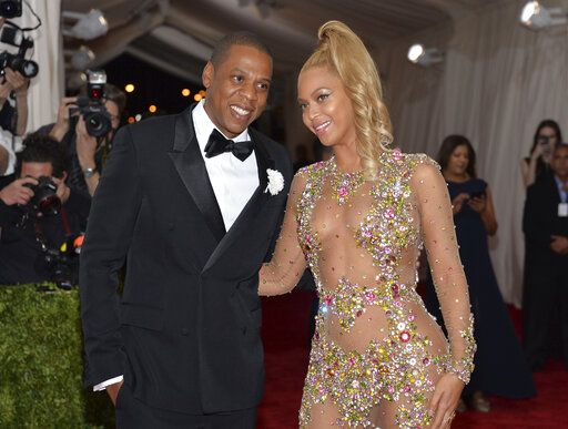 "FILE - In this May 4, 2015, file photo, Jay Z, left, and Beyonce arrive at The Metropolitan Museum of Art's Costume Institute benefit gala celebrating ""China: Through the Looking Glass"" in New York. Beyonce was nominated for nine Grammy Awards on Tuesday. She is tied with  Paul McCartney for the second-most nominated act in the history of the awards show with 79 nominations. Her husband Jay-Z and Quincy Jones, who have both earned 80 nominations each, are tied for first place. (Photo by Evan Agostini/Invision/AP, File)"