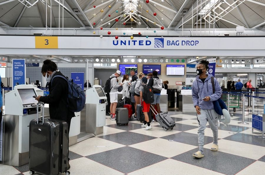 Pre-holiday travelers use kiosks and counters Friday at a terminal at O'Hare International Airport in Chicago. The recent weeks' soaring numbers of coronavirus cases in Illinois prompted Gov. J.B. Pritzker to urge against traveling from the airports.