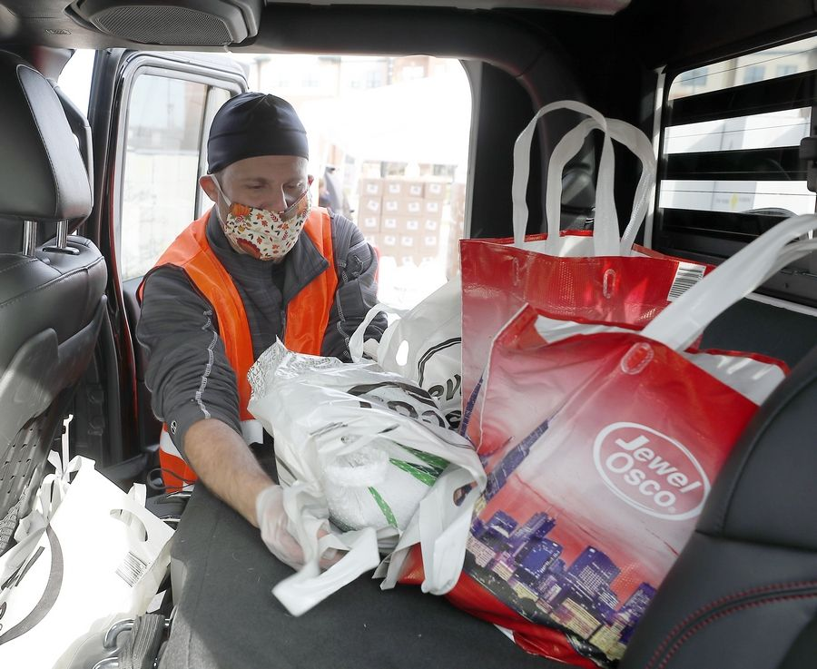 Volunteers mask up because of the COVID-19 pandemic but continue with a holiday tradition Saturday, the Basket Brigade of Suburban Chicago delivering Thanksgiving meals to needy residents.
