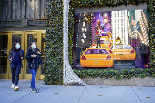 Black Friday shoppers wear face masks as the leave Saks Fifth Avenue flagships store empty handed, Friday, Nov. 27, 2020, in New York.