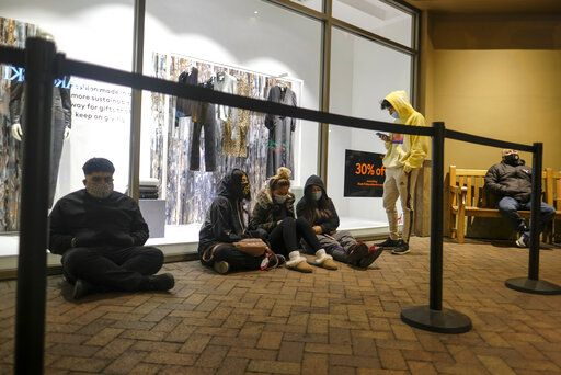 Black Friday shoppers wait in line to enter an shore that opened at 6am at the Citadel Outlets in Commerce, Calif., Friday, Nov. 27, 2020.