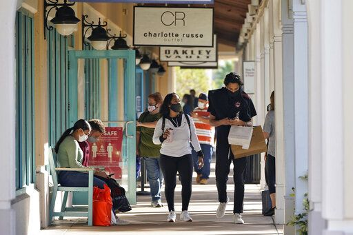 Shoppers wear protective face masks as they look for Black Friday deals at the Ellenton Premium Outlet stores Friday, Nov. 27, 2020, in Ellenton, Fla. Attendance at the mall was down in an attempt to avoid spreading the corona virus.