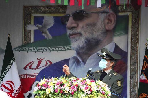 "In this photo released by the official website of the Iranian Defense Ministry, Defense Minister Gen. Amir Hatami speaks during a funeral ceremony for Mohsen Fakhrizadeh, a scientist who was killed on Friday, shown in the banner at background, in Tehran, Iran, Monday, Nov. 30, 2020. Iran held the funeral Monday for the slain scientist who founded its military nuclear program two decades ago, with the Islamic Republic's defense minister vowing to continue the man's work ""with more speed and more power."" (Iranian Defense Ministry via AP)"