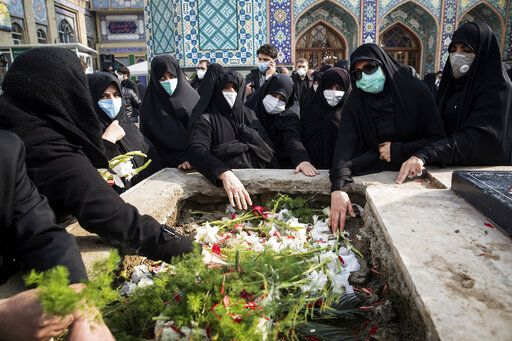 "People pray at the grave of Mohsen Fakhrizadeh, a scientist who was killed on Friday, during his burial in Tehran, Iran, Monday, Nov. 30, 2020. Iran held a funeral service Monday for the slain scientist who founded its military nuclear program two decades ago, with the Islamic Republic's defense minister vowing to continue the man's work ""with more speed and more power."" (Hamed Malekpour/Tasnim News Agency via AP)"