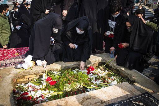 "People pray at the grave of Mohsen Fakhrizadeh, a scientist who was killed on Friday, during his burial in Tehran, Iran, Monday, Nov. 30, 2020. Iran held the funeral service Monday for the slain scientist who founded its military nuclear program two decades ago, with the Islamic Republic's defense minister vowing to continue the man's work ""with more speed and more power."" (Hamed Malekpour/Tasnim News Agency via AP)"