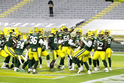 Green Bay Packers players help Preston Smith celebrate his touchdown on a fumble recovery during the first half of an NFL football game against the Chicago Bears Sunday, Nov. 29, 2020, in Green Bay, Wis.