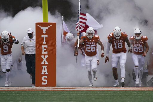 Texas head coach Tom Herman, second from left, and his players run onto the field for an NCAA college football game against Iowa State, Friday, Nov. 27, 2020, in Austin, Texas.