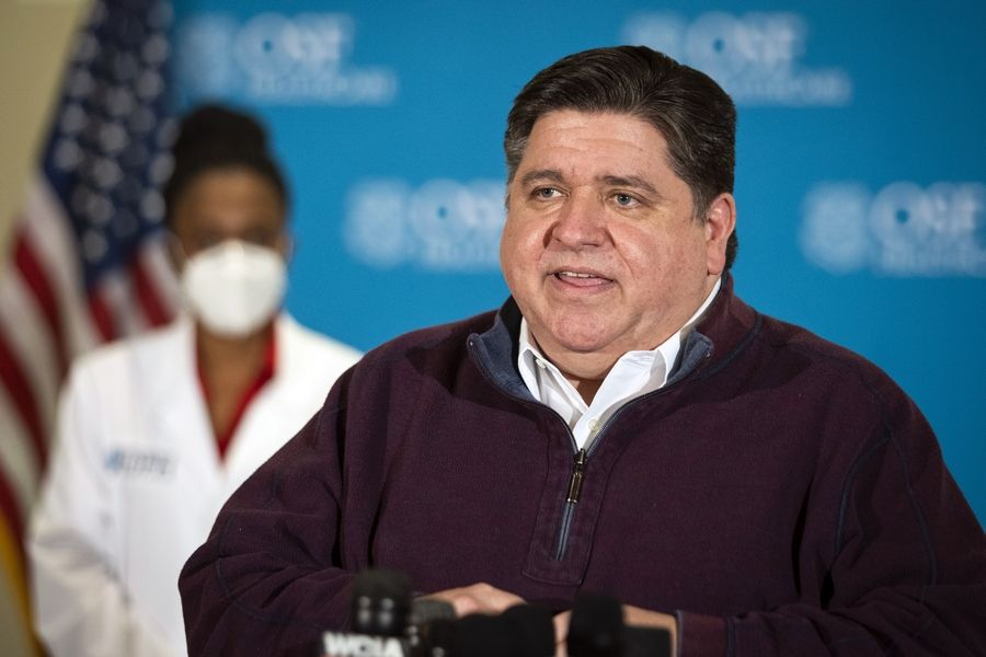 Gov. J.B. Pritzker speaks to reporters after a nurse administered Illinois' first five Pfizer-BioNTech COVID-19 vaccinations outside Chicago Tuesday morning at OSF Saint Francis Medical Center in Peoria, Ill.