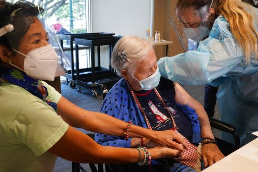 Patricia Wasseman, holds Hermina Levin's hands as nurse Eva Diaz administers the Pfizer vaccine at John Knox Village, Wednesday, Dec. 16, 2020, in Pompano Beach, Fla. Nursing home residents and health care workers in Florida began receiving the Pfizer vaccine this week.
