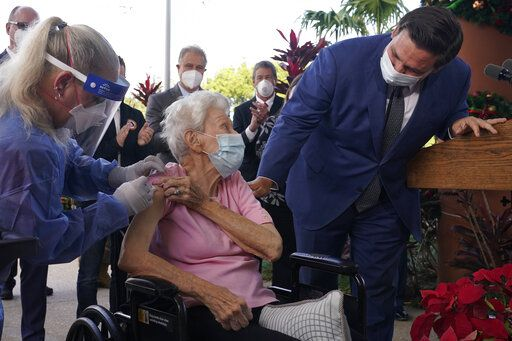 Florida Gov. Ron DeSantis asks Vera Leip, 88, how she feels after nurse Christine Philips, left, administered the Pfizer vaccine at John Knox Village, Wednesday, Dec. 16, 2020, in Pompano Beach, Fla. Nursing home residents and health care workers in Florida began receiving the Pfizer vaccine this week.