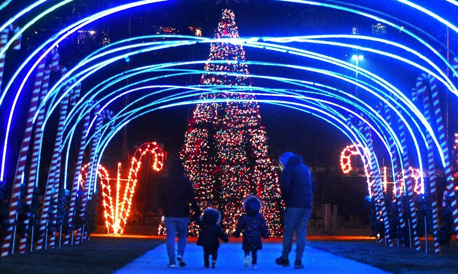A family walks through an arch of lights at Elgin's Festival of Lights.