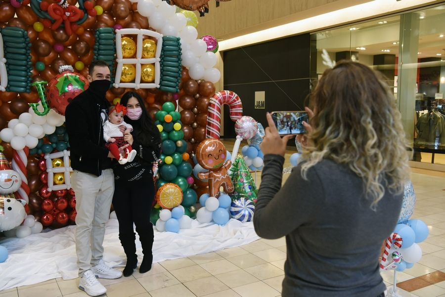 Megan Raysby takes a photo of Sam and Doris Pekovic of Prospect Heights and their daughter, Mila, 4 months, in front of a balloon sculpture of a gingerbread house at Northbrook court Mall Saturday. Raysby, of North Shore Balloon Decor, constructed the sculpture to help raise funds for the Hunger Resource Network.