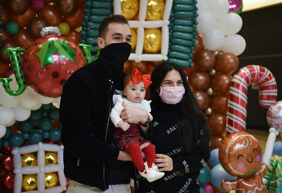 Sam and Doris Pekovic of Prospect Heights and their daughter, Mila, 4 months, have their photo taken in front of a balloon sculpture of a gingerbread house at Northbrook court Mall Saturday. Megan Raysby of North Shore Balloon Decor constructed the sculpture to help raise funds for the Hunger Resource Network.