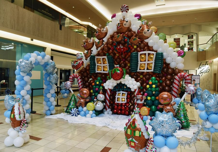 Megan Raysby of North Shore Balloon Decor constructed a balloon sculpture of a gingerbread house at Northbrook Court Mall to help raise funds for the Hunger Resource Network.
