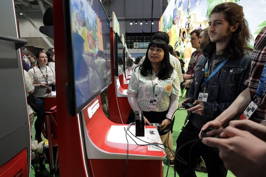 Visitors to the Pax East conference play the new Nintendo Switch video game Animal Crossing in Boston.