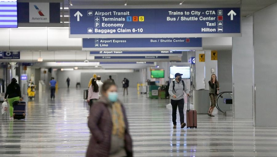 Masked Thanksgiving travelers walk through an unusually quiet O'Hare International Airport last month.