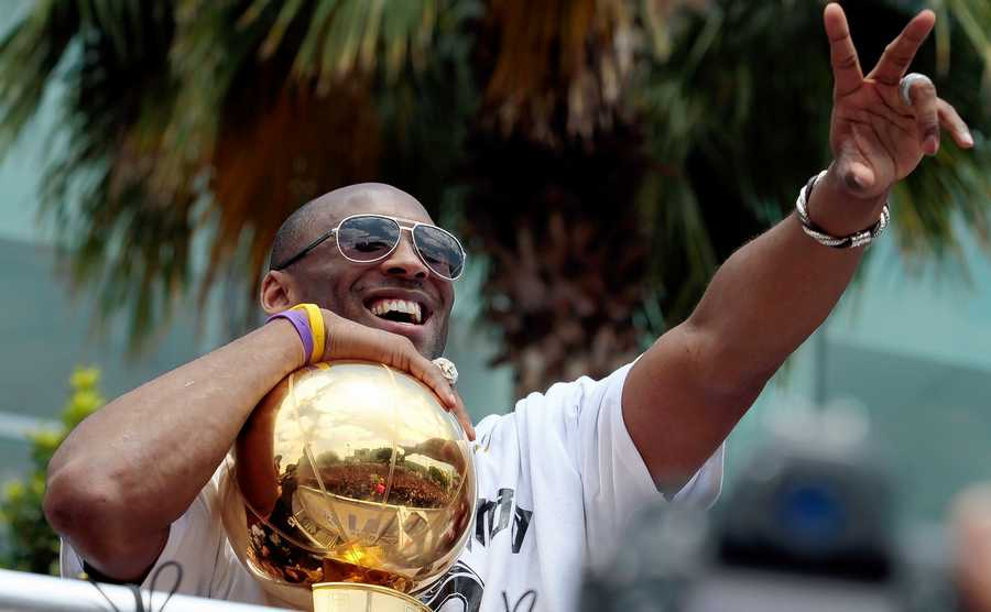 In this June 21, 2010, file photo, holding the NBA championship trophy, Los Angeles Lakers' Kobe Bryant flashes the victory sign during a parade in downtown Los Angeles. Bryant, the 18-time NBA All-Star who won five championships and became one of the greatest basketball players of his generation during a 20-year career with the Los Angeles Lakers, died in a helicopter crash Sunday, Jan. 26, 2020.