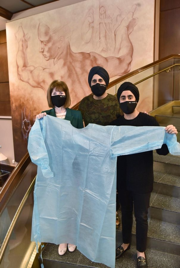 Faced with a shortage of PPE earlier this year, Edward-Elmhurst Health CEO Mary Lou Mastro, left, reached out to fashion designer Mac Duggal, middle, and his son, Yuvraj Duggal, who designed and created custom isolation gowns for hospital staff members.