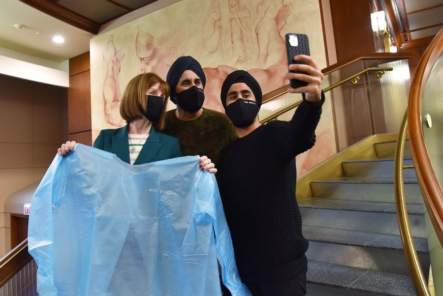 Yuvraj Duggal, right, takes a selfie with his father, fashion designer Mac Duggal, and Edward-Elmhurst CEO Mary Lou Mastro, who sought their help when the hospital system was running low on isolation gowns.
