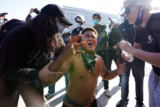 A counter demonstrator, center, yells after getting maced in the face by far-right demonstrators outside of City Hall Wednesday, Jan. 6, 2021, in Los Angeles. Demonstrators supporting President Donald Trump are gathering in various parts of Southern California as Congress debates to affirm President-elect Joe Biden's electoral college victory.
