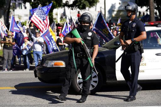 Police officers hold weapons in front of a crowd of President Donald Trump supporters outside of City Hall Wednesday, Jan. 6, 2021, in Los Angeles. Demonstrators supporting President Trump are gathering in various parts of Southern California as Congress debates to affirm President-elect Joe Biden's electoral college victory.